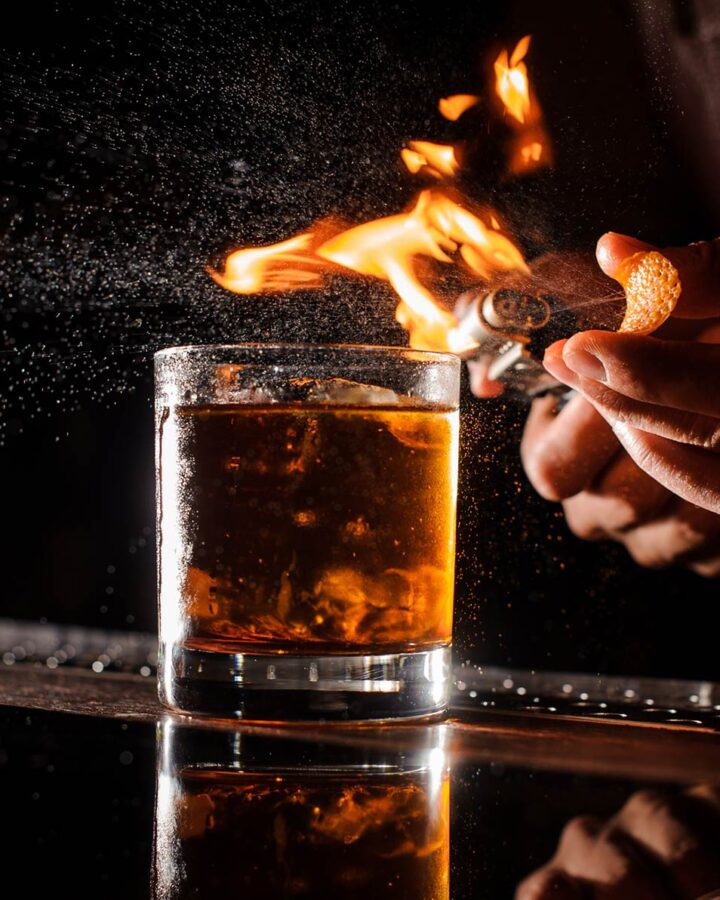 bartender using open flame to burn orange peel before adding to cocktail glass